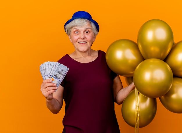 La donna anziana sorpresa che indossa il cappello del partito tiene i palloni dell'elio ed i soldi isolati sulla parete arancione con lo spazio della copia