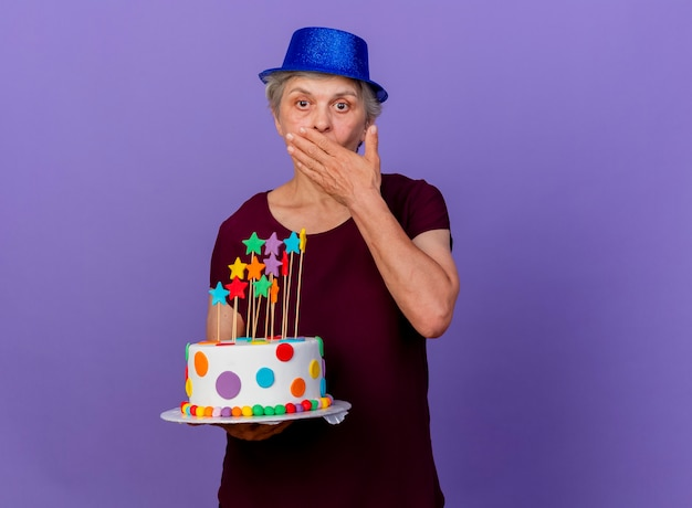 Surprised elderly woman wearing party hat puts hand on mouth and holds birthday cake isolated on purple wall with copy space