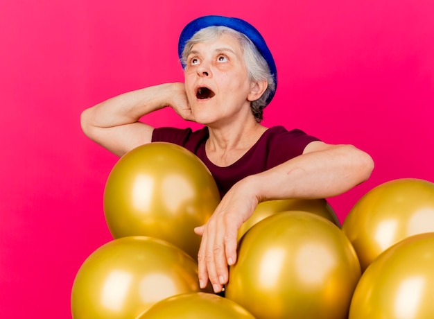 パーティーハットをかぶった驚いた年配の女性は、ヘリウム気球で立っている後ろに手を頭に置きます