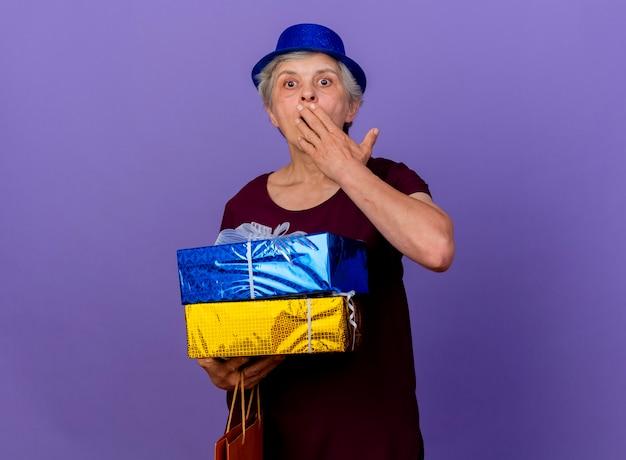 파티 모자를 쓰고 놀란 노인 여성은 복사 공간이 보라색 벽에 고립 된 선물 상자를 보유하고 입에 손을 넣습니다