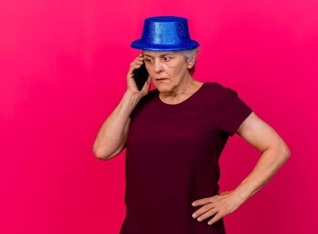 パーティーハットをかぶって驚いた年配の女性はピンクの電話で話している腰に手を置きます
