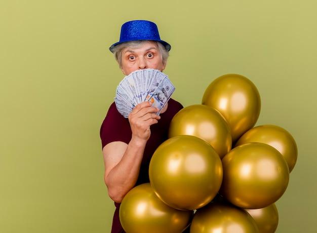 La donna anziana sorpresa che indossa il cappello del partito si leva in piedi lateralmente che tiene i palloni dell'elio ed i soldi isolati sulla parete verde oliva con lo spazio della copia