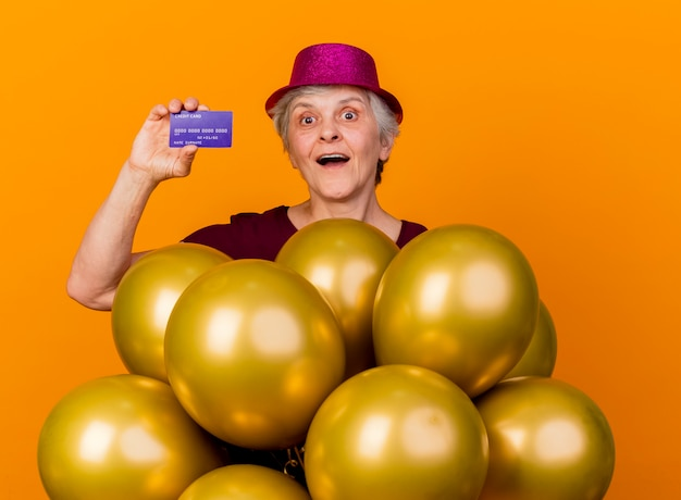 Удивленная пожилая женщина в партийной шляпе стоит с гелиевыми шарами и держит кредитную карту, изолированную на оранжевой стене