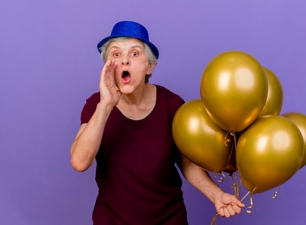 La donna anziana sorpresa che porta il cappello del partito sta con i palloni dell'elio che tengono la mano vicino alla bocca isolata sulla parete viola con lo spazio della copia