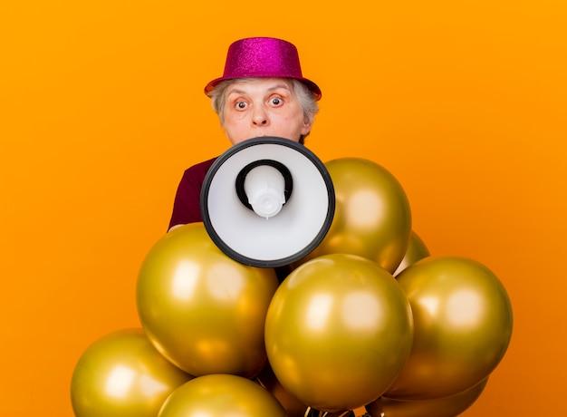 オレンジ色の壁に隔離されたラウドスピーカーを保持しているヘリウム気球とパーティーハットを身に着けている驚いた年配の女性