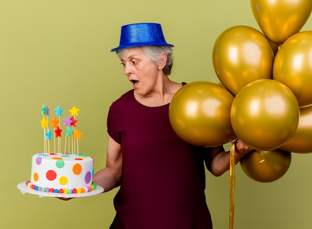 Surprised elderly woman wearing party hat stands with helium balloons looking at birthday cake on olive green