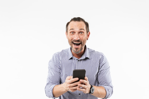 Surprised emotional adult man using mobile phone.