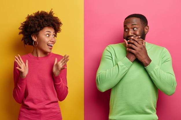 驚いた感情的なアフロアメリカ人女性は彼氏に面白い話をし、手のひらを上げ、黒い肌の男は笑い、口を覆い、感情を隠します