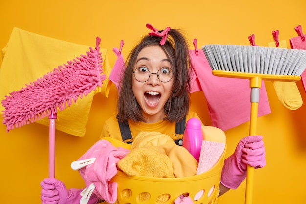 Surprised emotional brunette asian girl combs hair with clothespins holds mop and brush exclaims loudly wears round spectacles rubber gloves busy doing laundry poses against clothesline indoor