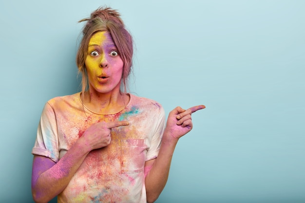 Surprised emotional female model has bated breath, dirty with colorful powder, has multicolored face, demonstrates something on blank space. holi festival celebration concept.