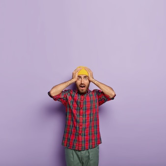 驚いた感情的な男は両手を頭に置き、黄色い帽子と市松模様のシャツを着て、上向きに驚いた