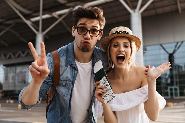 Удивленная эмоциональная счастливая пара туристов смотрит в камеру возле аэропорта