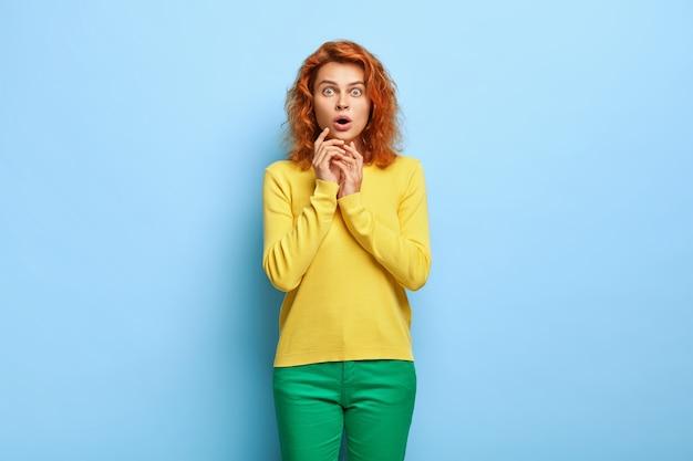Emozioni sorprese. la femmina dello zenzero impressionata stupita fissa con gli occhi azzurri