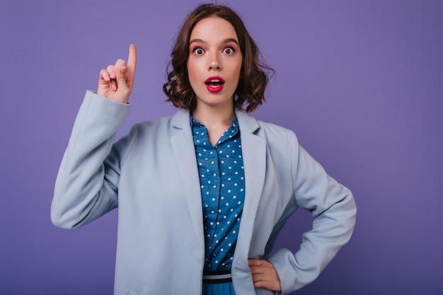 紫色の壁に立っている巻き毛の髪型で驚いた魅惑的な女性。驚きを表現する魅力的なヨーロッパの女の子の屋内ショット。