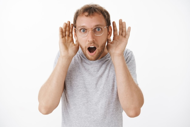 Surprised entertained handsome young male in gray t-shirt and glasses holding palms near ears to hear better dropping jaw while gossiping