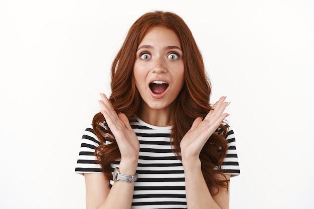 줄무늬 티셔츠를 입은 열광적인 귀여운 생강 소녀, 좋은 소식을 듣고 흥분하고 감동한 입을 벌리고, 헐떡이며, 숨막히는 복사 공간, 흰 벽을 응시하는 카메라