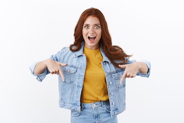 驚いた熱狂的な赤毛の女の子は、感動して驚いたように見え、驚くべきニュースを説明し、口を開けてあえぎながら魅了された凝視カメラを下のコピースペースを指していると説明します