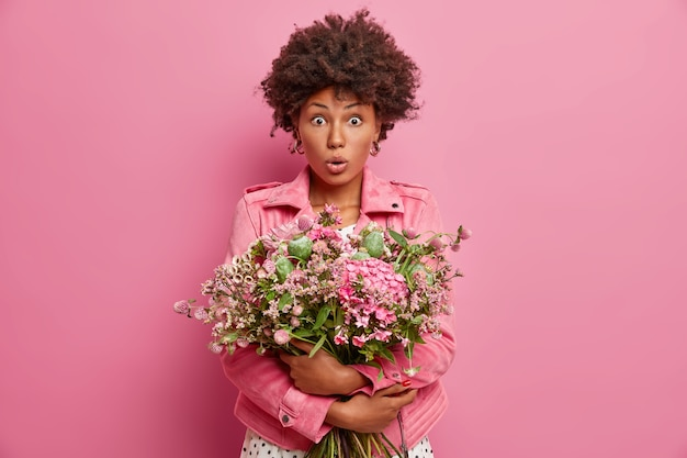 Surprised ethnic woman with floral bunch, has shocked expression, comes on romantic date, receieves unexpected proposal,