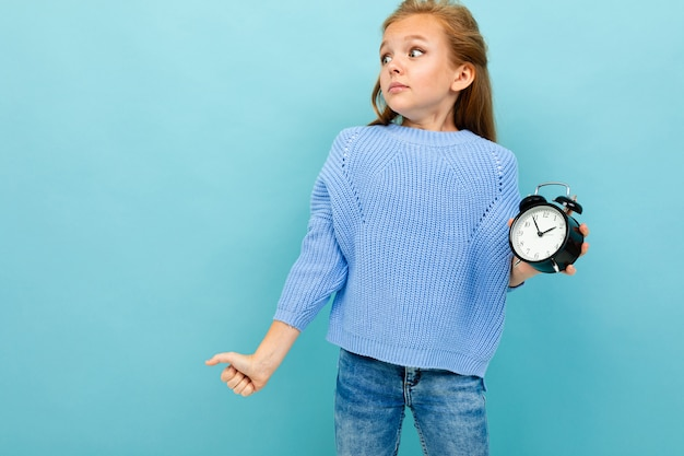 Surprised european girl holding an alarm clock on light blue