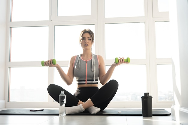 Surprised european sportswoman sitting on fitness mat and holding dumbbells at home. young pretty woman wear sportswear. concept of body figure care. interior of modern spacious apartment. sunny day