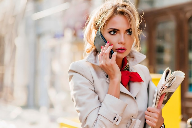 Surprised european woman looking away during phone conversation and walking down the street