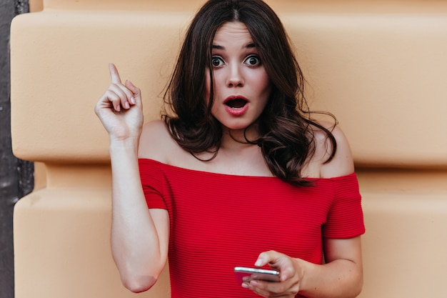 Donna europea sorpresa con il telefono in mano in posa davanti al muro. colpo esterno di stupita signora ben vestita con i capelli scuri.