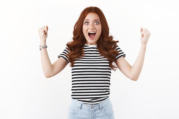 Удивленная, взволнованная и счастливая молодая рыжая женщина узнала, что выиграла в лотерею, накачивает воздух кулаками, смотрит в камеру, задыхаясь, на невероятные потрясающие новости, торжествует, празднует победу, белая стена
