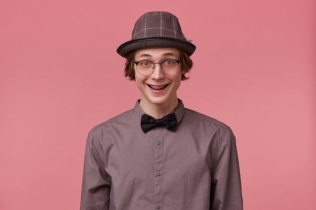 シャツの帽子と黒の蝶ネクタイを身に着けているスマートに服を着て、眼鏡をかけている驚いた興奮した魅力的な若い男は、ピンクの背景に分離された素敵な広い笑顔の歯列矯正ブラケットを持っています