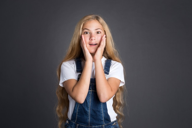 Surprised or excited beautiful teenage girl on grey background.