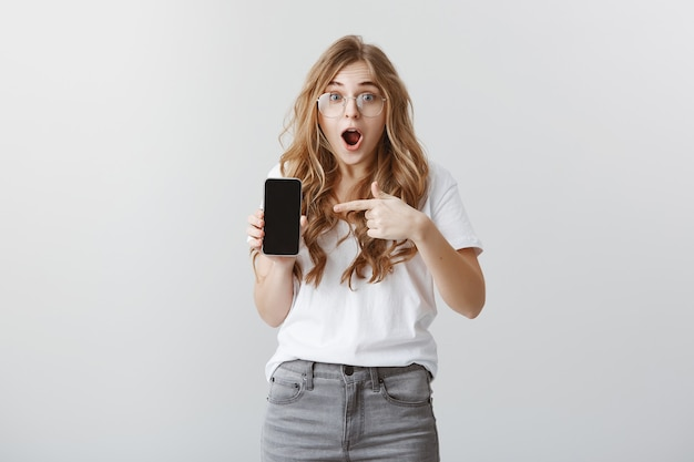 Surprised and excited blond girl in glasses pointing finger at mobile phone display, showing application