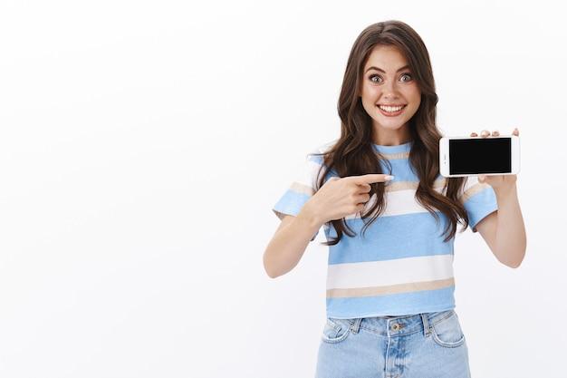 Sorpresa, eccitata, allegra, moderna, femmina, tenere lo smartphone in orizzontale, introdurre l'applicazione, indicare lo schermo del telefono cellulare divertito e soddisfatto, indicare un simpatico video internet, muro bianco