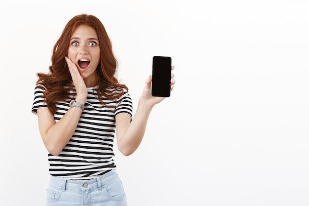 놀란 흥분한 귀여운 빨간 머리 소녀는 경외심과 감탄으로 헐떡거리고, 뺨을 만지고 감동을 받고, 턱을 괴고 카메라를 응시하고, 스마트폰 디스플레이에서 놀라운 제안을 보여주고, 충격을 받고 놀란 반응을 합니다.