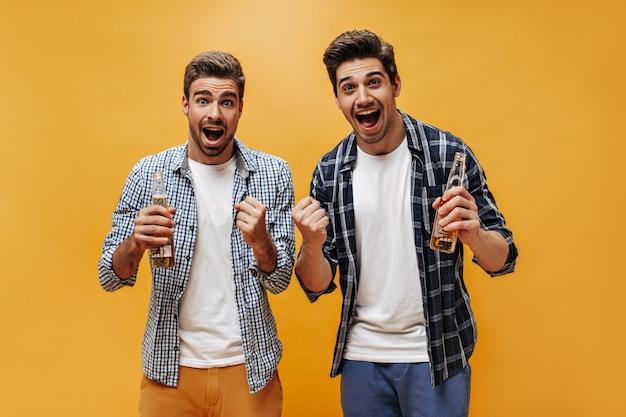 Sorpresi eccitati uomini felici in magliette bianche e camicie a scacchi si rallegrano, guardano nella telecamera e tengono bottiglie di birra sul muro arancione.
