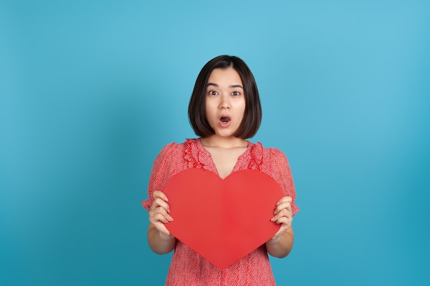 Surprised excited impressed young asian woman with open mouth  holding big red paper heart