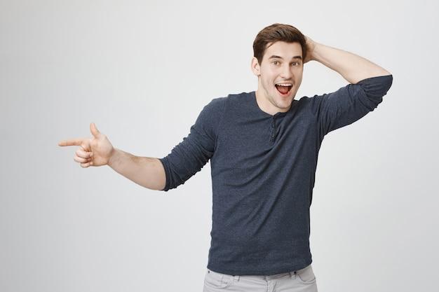 Uomo eccitato sorpreso che sorride e che indica a sinistra