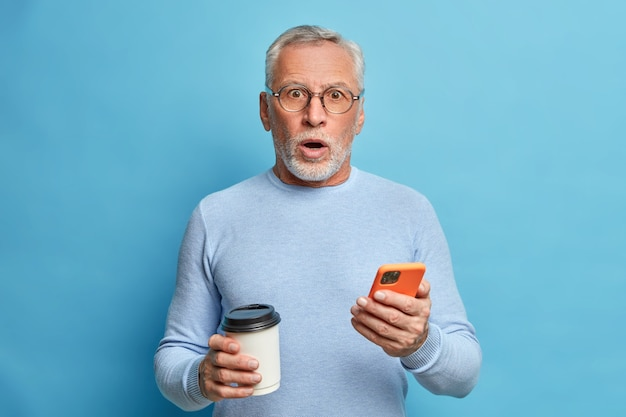 Surprised excited mature man gasps from amazement holds smartphone and reads news drinks coffee to go receives unexpected news wears casual jumper isolated over blue wall