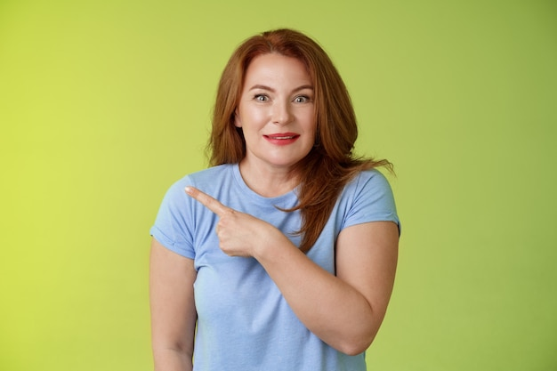 놀란 흥분된 중년 궁금 빨간 머리 여자 가리키는 왼쪽 즐겁게 서 흥분 즐거운 녹색 벽 봐 카메라 호기심 관심