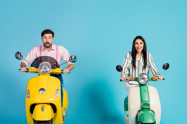 Surprised excited wife husband drive choppers see incredible sales news ads impressed scream wow omg wear striped pink shirt isolated over blue color wall