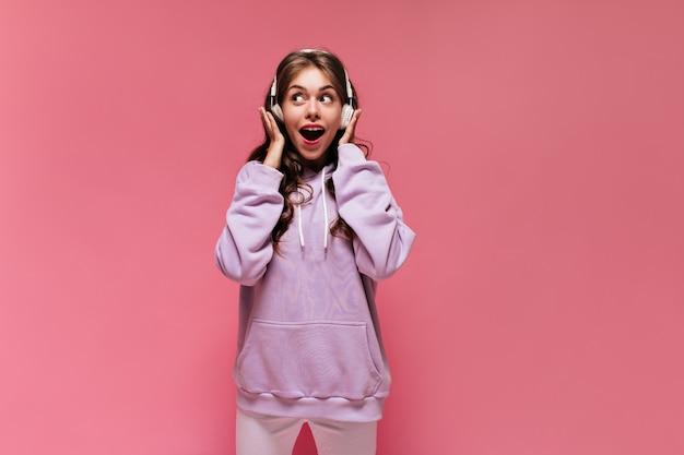 Удивленная возбужденная женщина в фиолетовой толстовке с капюшоном и белых штанах слушает музыку в наушниках