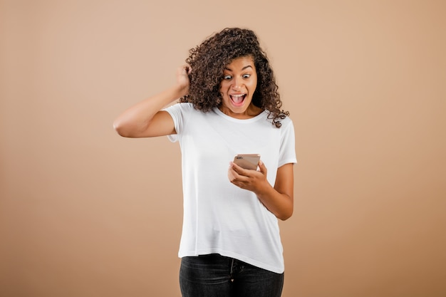 Surprised excited young black girl with phone in hand isolated over brown