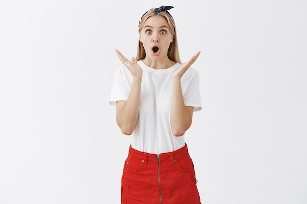 Surprised and excited young blond girl posing against the white wall