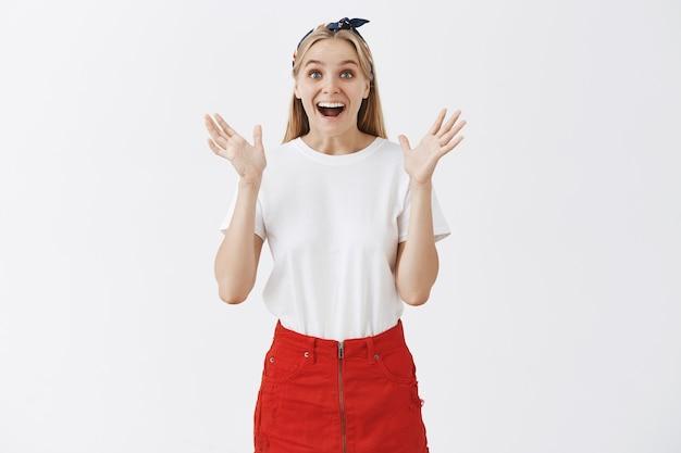 Giovane ragazza bionda sorpresa ed emozionata che posa contro il muro bianco