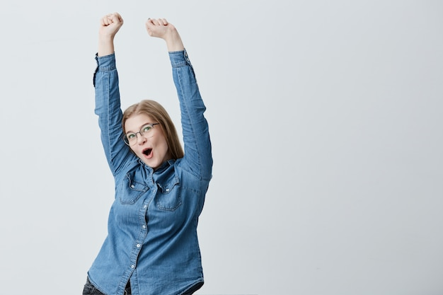 Surprised excited young female with blonde straight hair, spectacles, in denim shirt raises arms in the air, celebrating her triumph. happy blonde young female rejoicing her success.