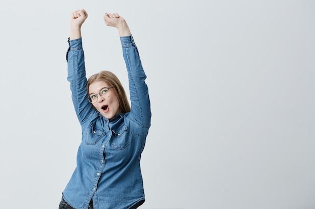 金髪のストレートヘア、眼鏡、デニムシャツを着た驚いて興奮した若い女性は、彼女の勝利を祝って空中で腕を上げます。彼女の成功を喜んで幸せな金髪の若い女性。
