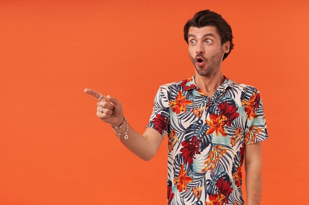 Surprised excited young man with bristle in colourful shirt looking to the side and pointing at copyspace