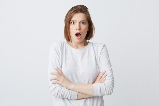 Удивленная возбужденная молодая женщина в лонгсливе с открытым ртом, стоя со скрещенными руками