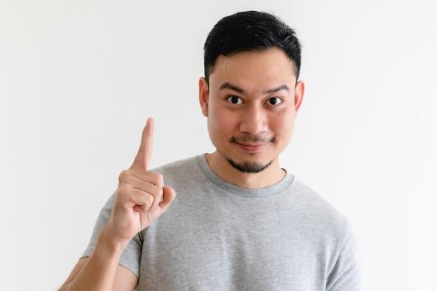 Человек с удивленным лицом азиатский делая знак рукой номер на изолированной белой предпосылке.