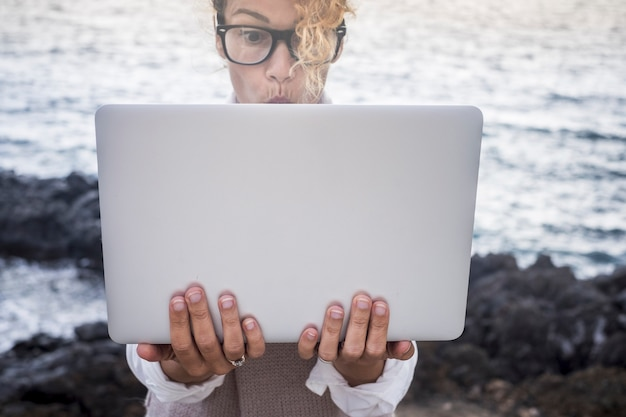 Surprised face expression for beautiful caucasian young woman work on a laptop in alternative office outdoor on the coastline near the ocean waves
