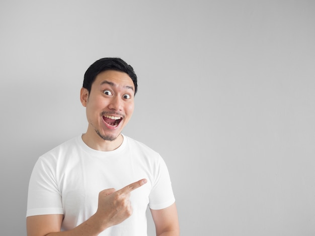 Surprised face of happy asian man in white shirt  light grey background.