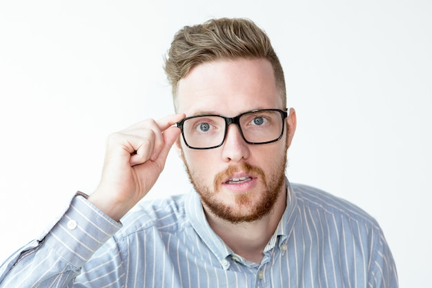 Surprised face of man looking through glasses